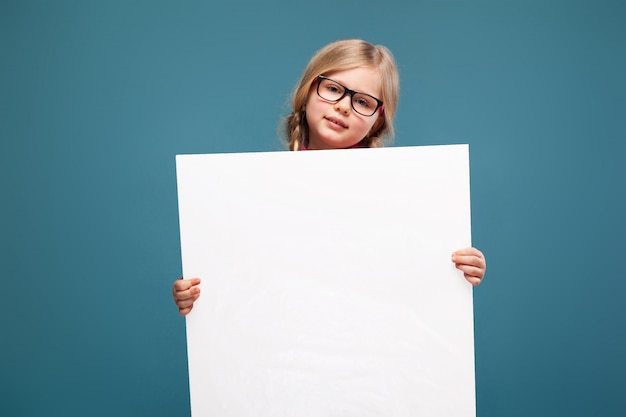 La bambina adorabile in camicia rosa, pantaloni neri e vetri tiene il cartello in bianco vuoto