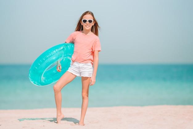 La bambina adorabile si diverte alla spiaggia tropicale durante la vacanza