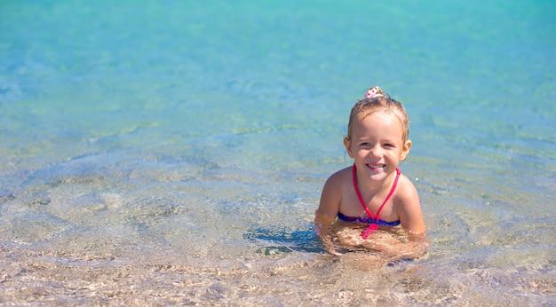 La bambina adorabile si diverte alla spiaggia tropicale