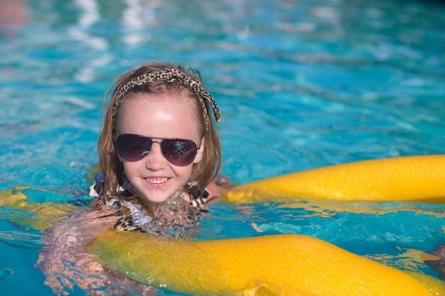 La bambina adorabile si diverte in piscina