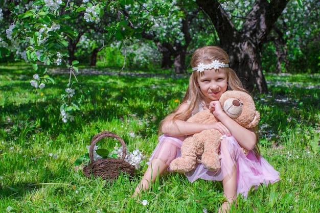 La bambina adorabile si diverte nel meleto sbocciante