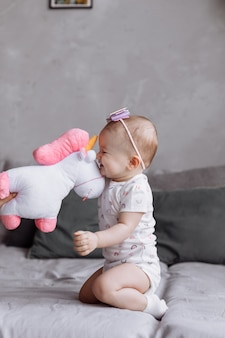 La bambina adorabile sta giocando con l'unicorno del giocattolo sul letto a casa. concetto di giorno dell'infanzia. bambino felice, giorno della famiglia