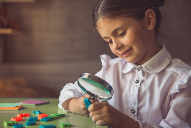 La bambina affascinante in uniforme scolastico sta sorridendo.