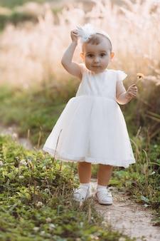 La bambina affascinante in vestito bianco cammina lungo il percorso nel campo