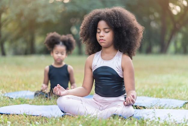 La bambina afroamericana che si siede sulla pratica della stuoia del rotolo medita l'yoga nel parco all'aperto