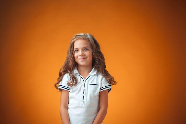 La bambina allegra carina su sfondo arancione