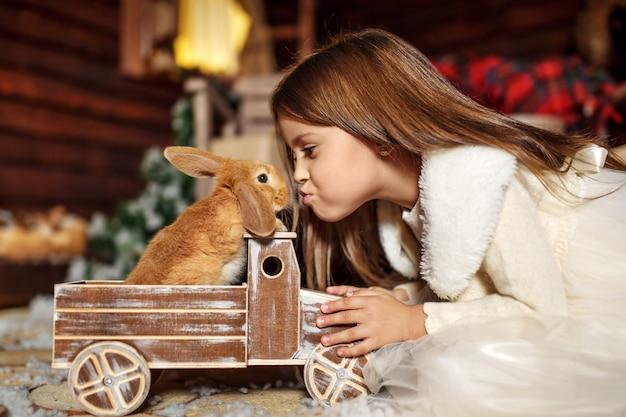 La bambina allunga per baciare un coniglio che si siede in un'automobile del giocattolo. decorazione natalizia. concetto di vacanza