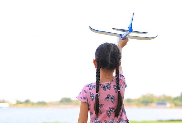 La bambina alza in su un aeroplano blu del giocattolo