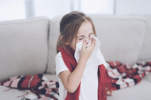 La bambina ammalata si siede su un divano bianco avvolto in una sciarpa rossa.