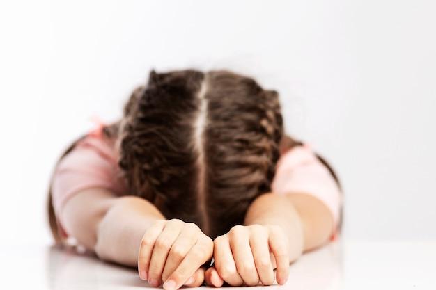 La bambina appoggiò la testa sul tavolo. muro bianco. avvicinamento.