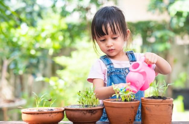 La bambina asiatica adorabile di 3 anni sta innaffiando la pianta nei vasi
