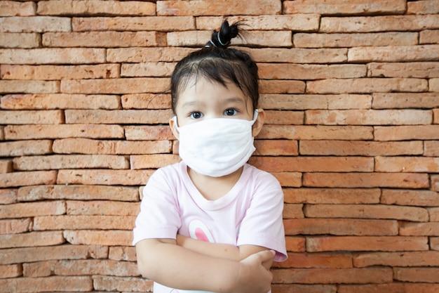 La bambina asiatica che indossa una maschera protettiva resta a casa per proteggere il coronavirus covid-19 e l'inquinamento da smog dell'aria con pm 2.5. anti smog e virus. inquinamento atmosferico e concetto medico.