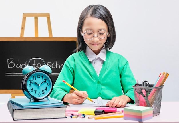 La bambina asiatica con stazionario scrive nel libro sul tavolo