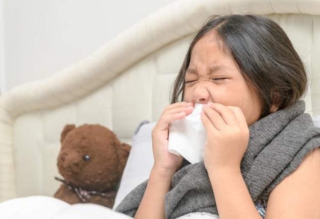 La bambina asiatica ha il naso che cola e soffia il naso nel tessuto