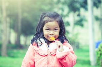 La bambina asiatica sveglia sta mangiando il gelato nel parco nel filtro colorato d'annata