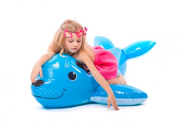 La bambina attraente in bikini nero, gonna rosa e corona rosa si trova sulla guarnizione gonfiabile