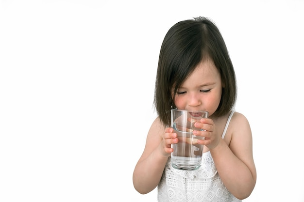 La bambina beve acqua da una tazza di vetro.