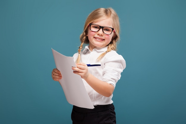 La bambina carina e carina in camicia bianca, occhiali e pantaloni neri tiene le carte