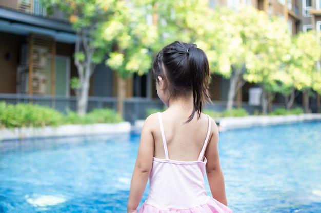La bambina carina posteriore si sente felice giocare e nuotare in piscina