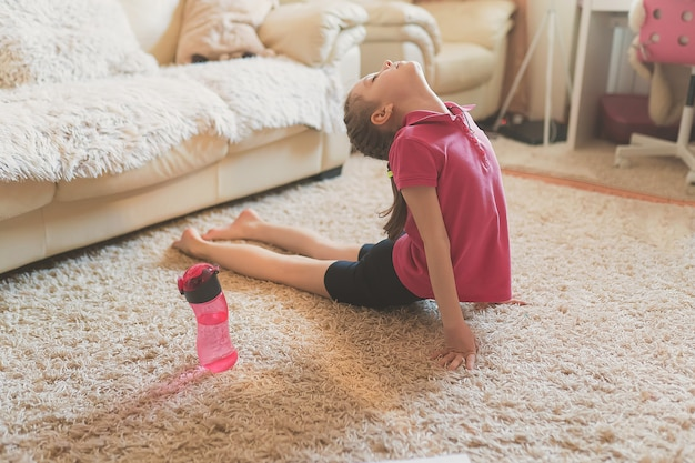 La bambina carina sta praticando ginnastica a casa