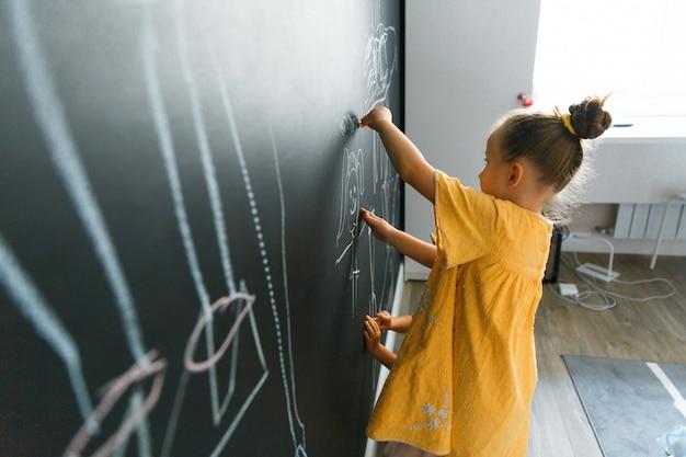 La bambina caucasica disegna sulla parete con la lavagna