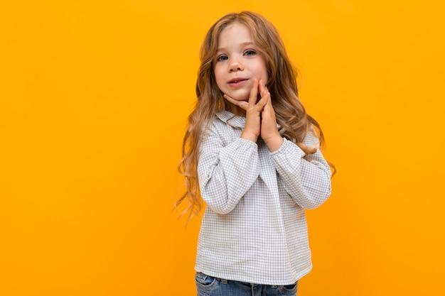 La bambina caucasica è abbracciata sulla parete gialla