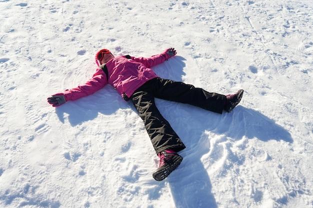 La bambina che fa uno snowangel che indossa la neve copre