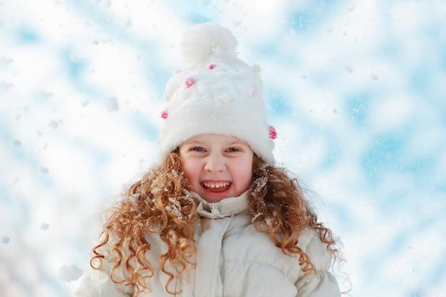 La bambina che gode della natura su un inverno cammina nel giorno soleggiato.