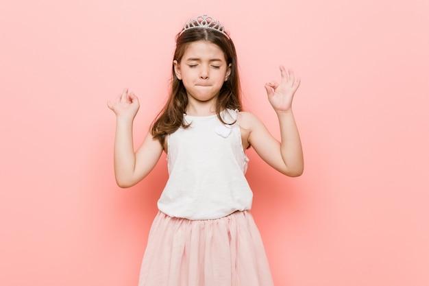La bambina che indossa un look da principessa si rilassa dopo una dura giornata di lavoro, sta eseguendo yoga.