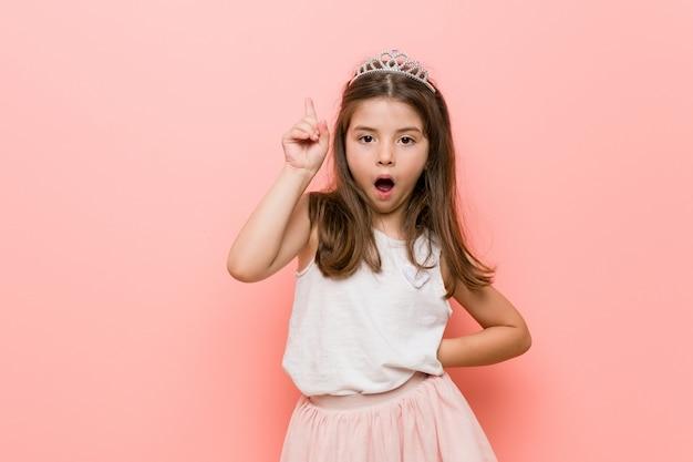 La bambina che indossa una principessa guarda avendo una grande idea, concetto di creatività.