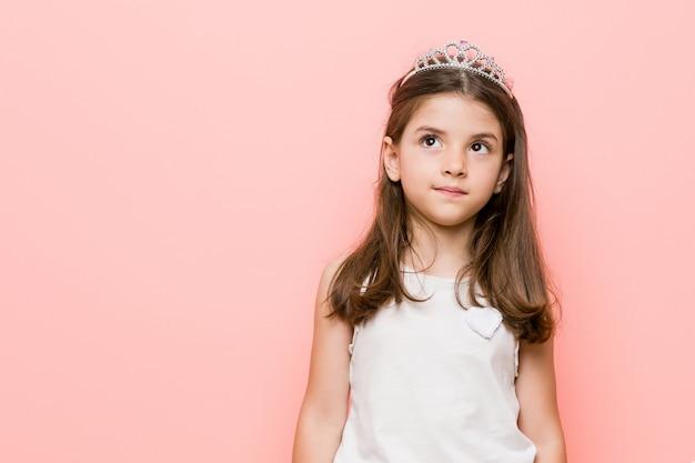 La bambina che indossa una principessa sembra sognare di raggiungere obiettivi e scopi