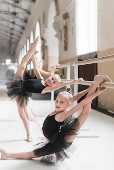 La bambina che si esercita in balletto balla con i suoi amici nello studio di ballo