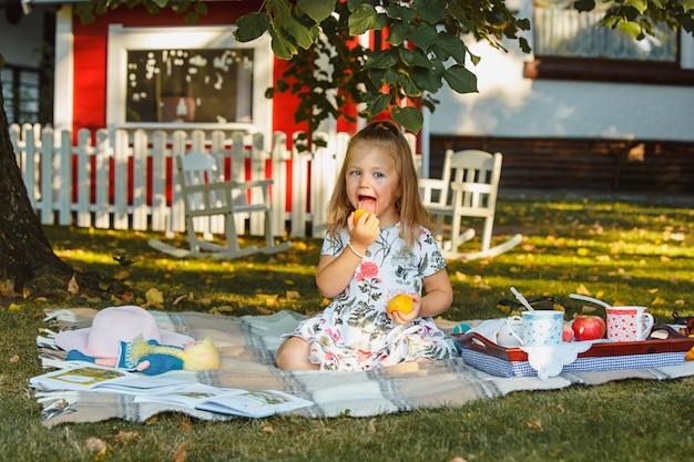 La bambina che si siede sull'erba verde