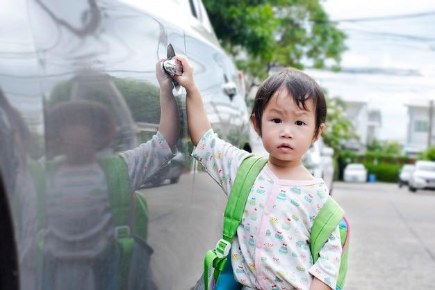 La bambina chiude la portiera della macchina per andare a scuola. bambino che gioca all'aperto a scuola.