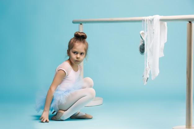 La bambina come ballerina della ballerina che posa vicino allo scaffale di balletto sullo studio blu