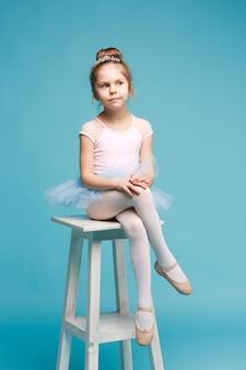 La bambina come ballerina della ballerina che si siede sulla sedia di legno bianca allo studio blu