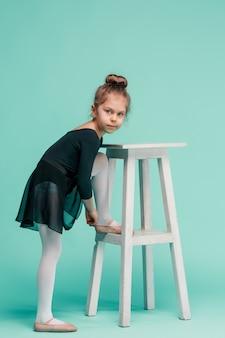 La bambina come ballerina della ballerina vicino alla sedia sullo studio blu
