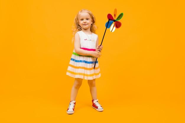 La bambina con capelli biondi tiene un'elica rotonda del giocattolo su una priorità bassa gialla