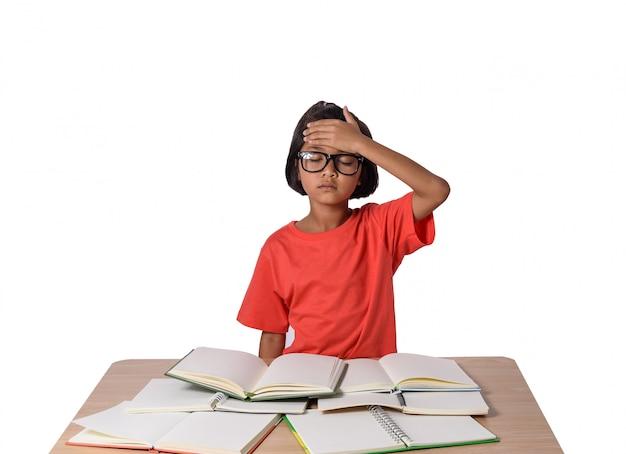 La bambina con gli occhiali ha pensato e molti prenotano sulla tavola. di nuovo al concetto di scuola, isolato su bianco