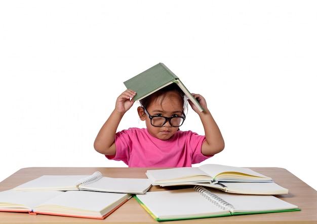 La bambina con gli occhiali ha pensato e molti prenotano sulla tavola. di nuovo al concetto di scuola, isolato su sfondo bianco