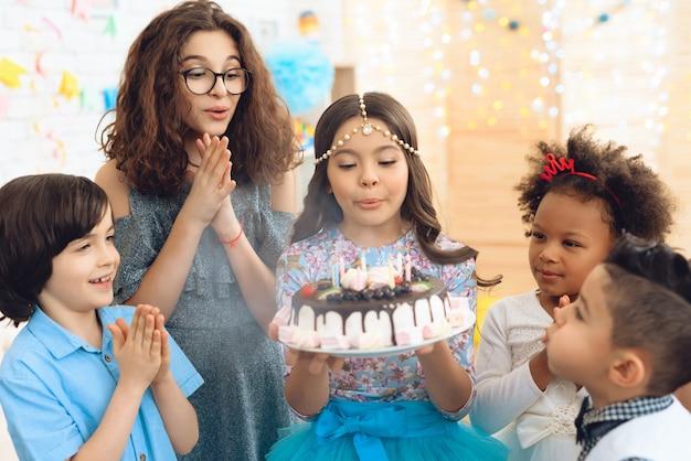 La bambina con il copricapo soffia le candele