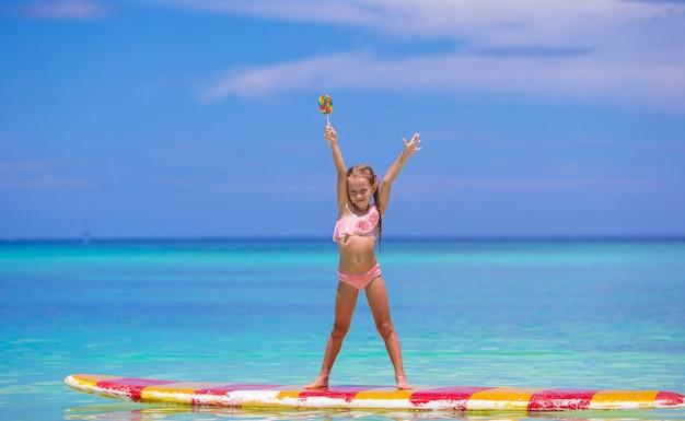 La bambina con il lecca-lecca si diverte sulla tavola da surf nel mare