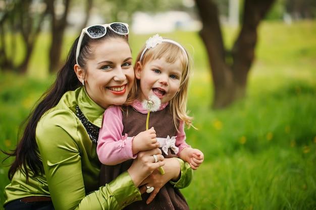 La bambina con la madre soffia un dente di leone all'aperto