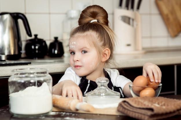 La bambina con la preparazione cuoce la torta casalinga di festa in cucina.