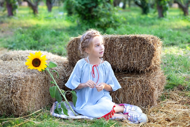 La bambina con la treccia sulla sua testa si siede su rotolo dei mucchi di fieno in giardino e tiene il girasole. giovane ragazza bionda del ritratto con il girasole
