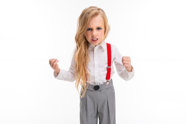 La bambina con lunghi capelli biondi in una camicia bianca, i pull-up rossi, i pantaloni in una gabbia, i calzini rossi e le scarpe con il trucco luminoso è arrabbiata.