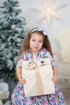 La bambina con un grande regalo di natale posa vicino all'albero di natale.