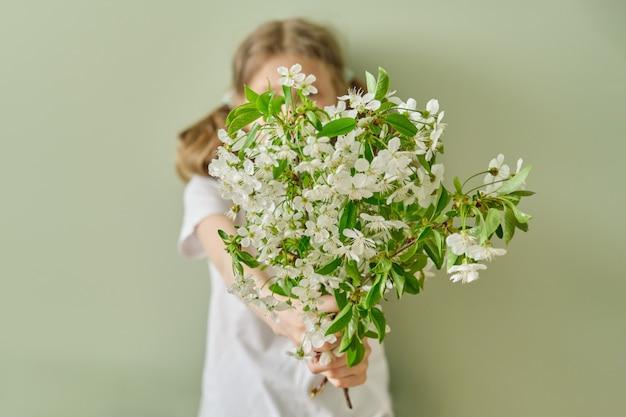 La bambina dà ai fiori bianchi di primavera rami di ciliegio in fiore