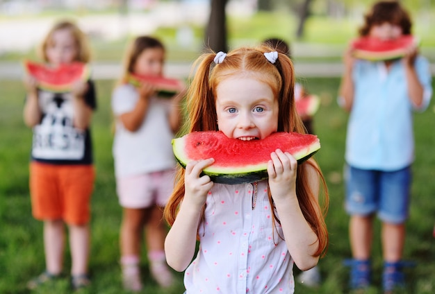 La bambina dai capelli rossi mangia avidamente anguria matura succosa