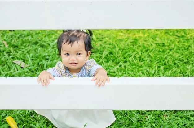 La bambina del primo piano prende un recinto bianco sul pavimento dell'erba nei precedenti del giardino con il fronte di sorriso